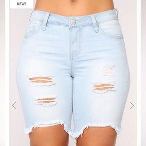 Mid rise light wash distressed Bermuda jean shorts